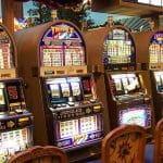 Fünf Spielautomaten aufgereiht in einem Casino.