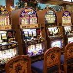 Fünf Spielautomaten in einem Spielcasino.