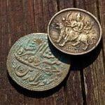 Alte Münzen auf einem Holztisch.