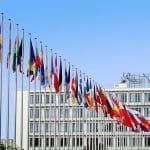 Flaggen der EU-Staaten vor einem Gebäude.