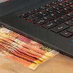 Geld wird in einen Laptop eingeführt.