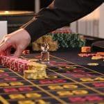 Croupier platziert Einsätze an einem Roulette-Tisch.