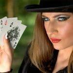 Eine junge Frau hält 5 ASS-Karten in der Hand.
