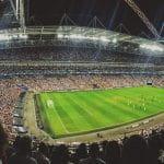 Volles Fußballstadion bei laufendem Spiel.
