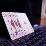 Fünf Pokerkarten stehen auf einem offenen Laptop.