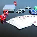 Pokerkarten, Würfel und Chips auf einem Spieltisch.