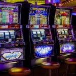 Drei Spielautomaten stehen nebeneinander in einer Spielhalle.