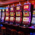 Sechs Spielautomaten stehen in einer Spielhalle nebeneinander.