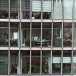Bürokomplex mit Glasfassade und Mitarbeitern in Büros.