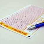 Ein Kugelschreiber liegt auf einem Lottoschein, bei dem vier Felder ausgefüllt wurden.