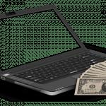Dollar-Banknoten liegen am Rand eines geöffneten Laptops.
