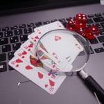 Fünf Pokerkarten, eine Lupe und vier Würfel liegen auf einer Computertastatur.