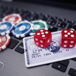 Auf einer Laptop-Tastatur liegen eine Kreditkarte, zwei rote Würfel und Spielchips.