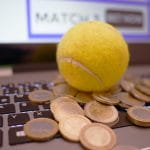 Auf einer Computertastatur liegt ein gelber Tennisball. Unter dem Ball liegen viele 1- und 2-Euro-Münzen.