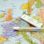 Auf einer Weltkarte liegt ein Corona-Schnelltest mit negativen Ergebnis und ein Plastikröhrchen.