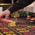 Ein Roulettetisch, bei dem zahlreiche Spielchips gesetzt wurden. Eine rechte Hand setzt gerade neue Chips.