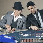 Zwei Männer im Anzug und Trinkgläsern sitzen an einem Pokertisch, auf dem Spielchips und einzelne Karten liegen.