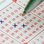 Ein roter Lottoschein, auf dem bereits drei Zahlen angekreuzt wurden. Ein Kugelschreiber schwebt über dem Lottoschein.