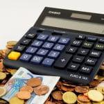 Auf einem Haufen mit Münzen und Geldscheinen liegt ein Taschenrechner.