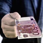 Eine Person hält mehrere 500-Euro-Scheine in der Hand.