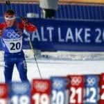 Ein Biathlon-Athlet beim Langlaufen vor einem Plakat mit der Aufschrift Salt Lake 2002.