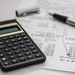 Auf einem Berechnungsbogen liegt ein Taschenrechner und ein Kugelschreiber.