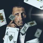 Vor einem ernst schauenden Mann fliegen mehrere Pokerkarten durch die Luft.
