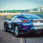 Ein blaues Rennauto, das sich allein auf einer Rennstrecke befindet und kleine Aufkleber von Silverstone und Pirelli hat.