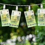 Sechs 100-Euro-Scheine hängen auf einer Wäscheleine zum Trocknen.