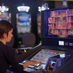 Eine Person spielt in einer Spielhalle an einem Automaten.
