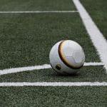 Ein Fußball liegt im eingezeichneten Eck eines Fußballfeldes.