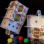 Aus mehreren Pokerkarten wurden zwei mehrstöckige Kartenhäuser gebaut. Davor liegen fünf Würfel mit unterschiedlichen Farben.