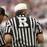 Drei Schiedsrichter stehen nebeneinander und sind von hinten zu sehen.
