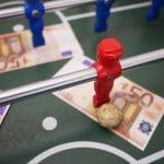 Auf einem Soccertisch liegen drei 50-Euro Scheine. Der roter Spieler hat den Ball.
