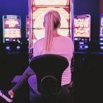 Eine Frau spielt an einem Automaten in einer Spielhalle.