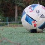Ein Fußball mit Werbung von Adidas und UEFA liegt auf einem Fußballrasen.