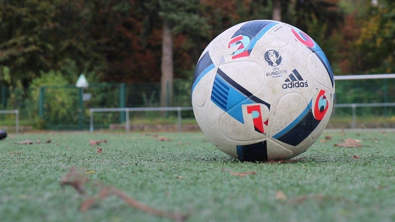 Bola sepak dengan iklan dari Adidas dan UEFA terletak di lapangan sepak bola.