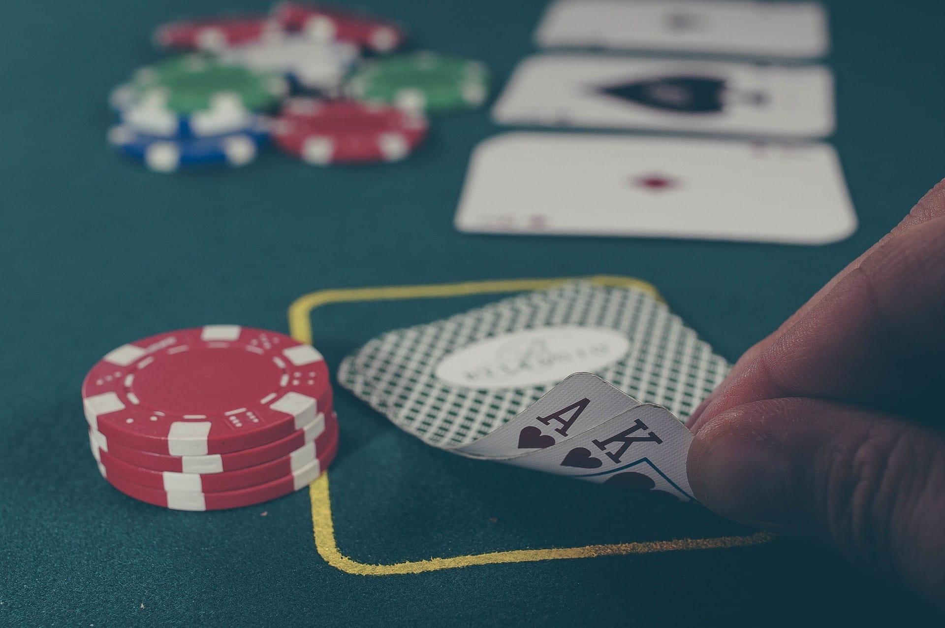 Seorang pemain melihat kartu remi tanpa benar-benar mengungkapkannya.  Ada beberapa chip game di sebelahnya.