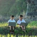 Zwei Kinder sitzen mit je einem Laptop auf dem Schoß in einer Wiese.