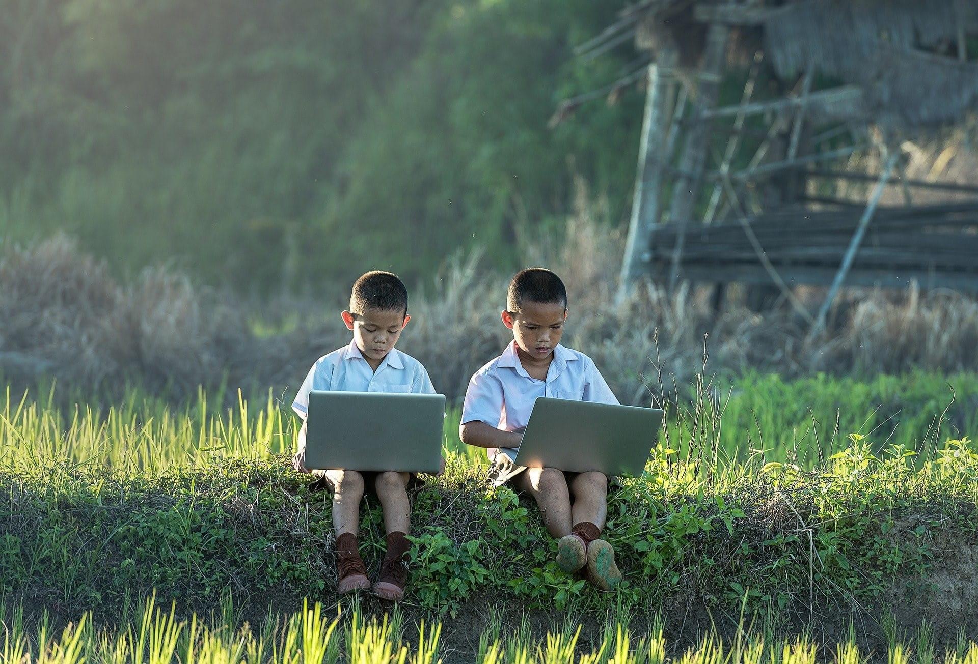 Dua anak sedang duduk di padang rumput, masing-masing dengan laptop di pangkuan mereka.