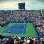 Ein vollbesetztes Stadion eines Tennisturniers – zwei Spieler sind gerade beim Spielen.