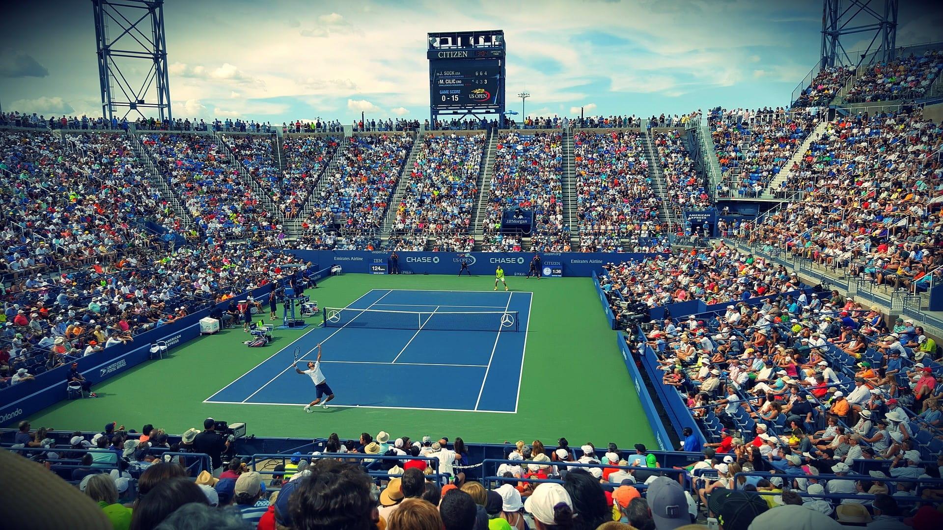 Stadion penuh turnamen tenis - dua pemain sedang bermain.