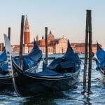 Im Hintergrund ist Venedig zu sehen – im Vordergrund stehen drei Gondeln auf dem Wasser.