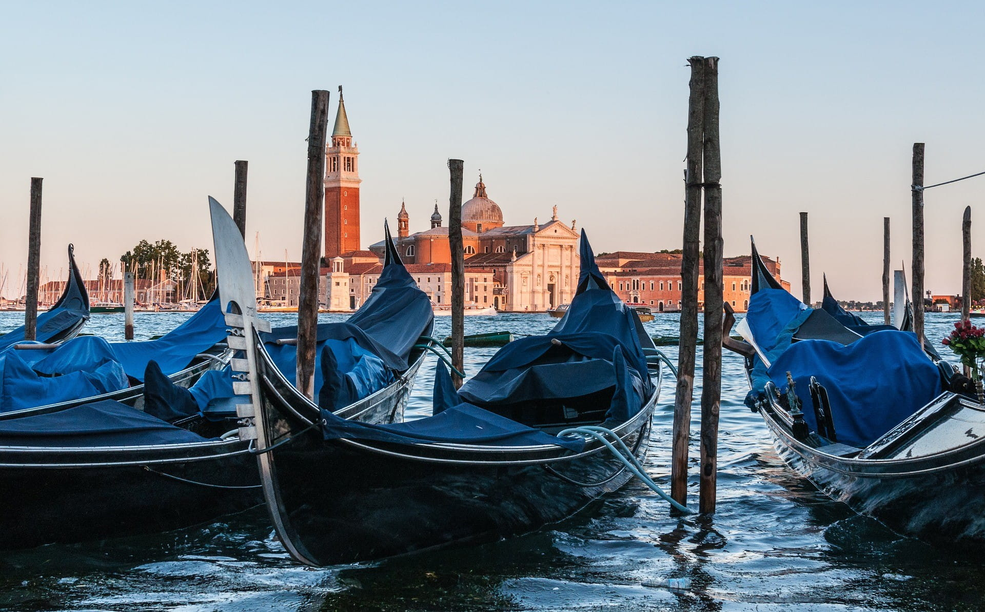 Venesia dapat dilihat di latar belakang - di latar depan ada tiga gondola di atas air.