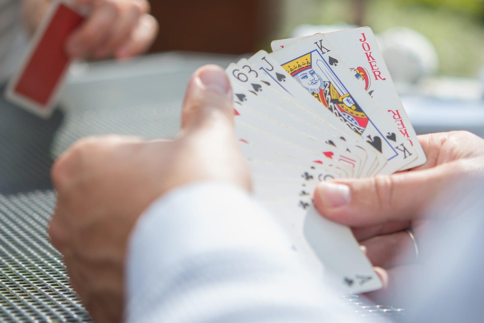 Dua pria memegang kartu poker di tangan mereka.  Dalam kasus seorang pria, kartu terlihat.